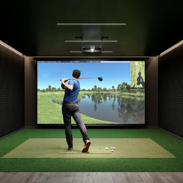 Golf simulator featuring man in blue shirt practicing in front of a screen depicting a golf course.