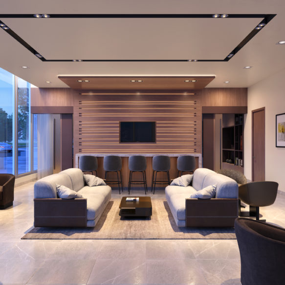 Brightly lit lounge featuring plush grey seating, floor-to-ceiling windows and a bar featuring a TV with decorative wooden surround.