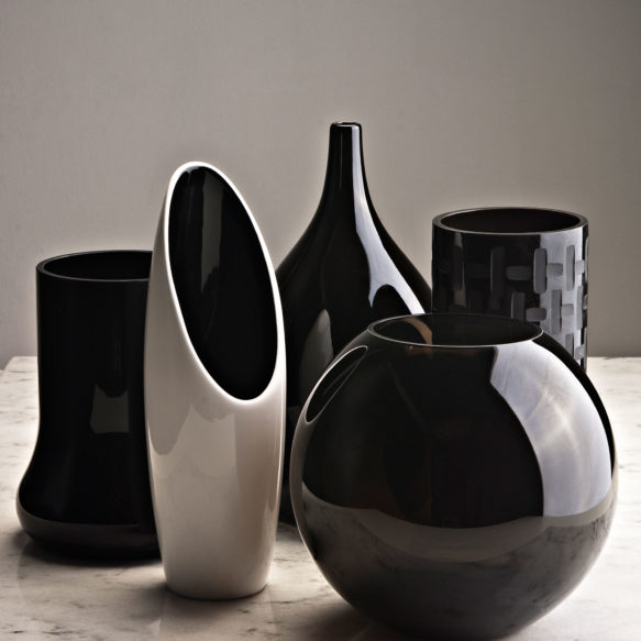 Decorative black and white vases on light grey marble surface.