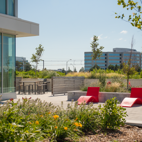 Elevated outdoor amenity featuring flower garden and two red, modern lounge chairs.