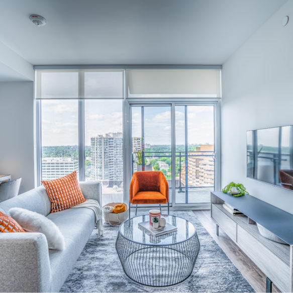 Suite featuring a bright white living room with orange accessories and floor-to-ceiling windows.