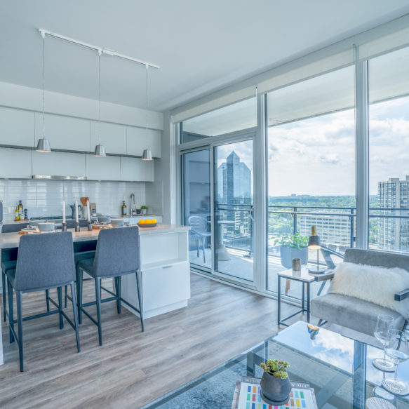 Suite featuring bright white kitchen finishes and living room accessories and floor-to-ceiling windows.