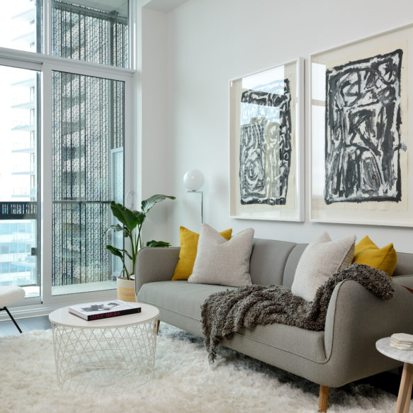 A bright living room with floor-to-ceiling windows featuring a grey couch, a small white chair and a circular coffee table.
