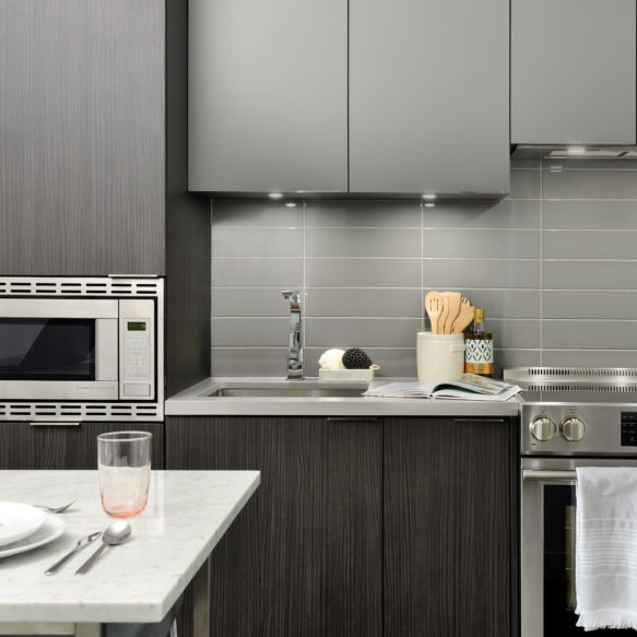 Kitchen featuring grey subway tile backsplash, dark grey cabinetry and stainless-steel appliances.