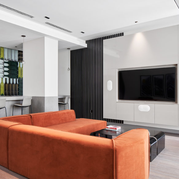 Bright, contemporary lounge featuring large screen tv, orange couch, bar and wall art with wine bottles.