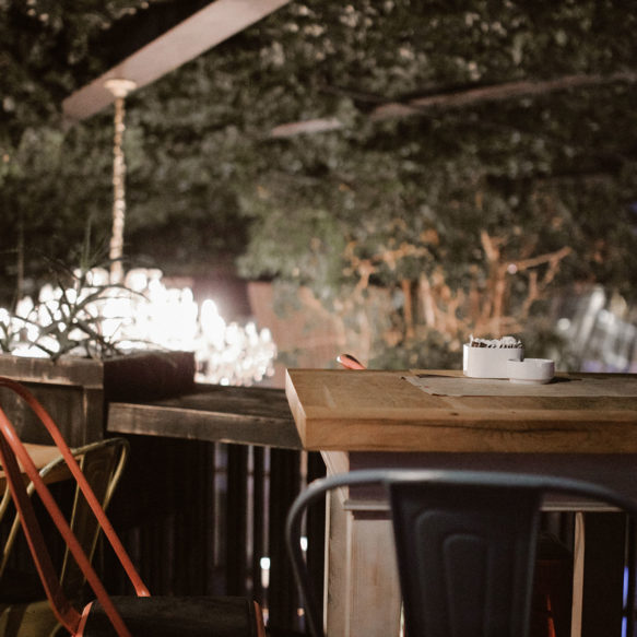 A café patio at night featuring eclectic outdoor seating, greenery and worn wooden tables.