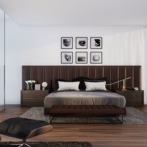 A bright bedroom featuring a large leather headboard and ottoman and a large black and white painting.