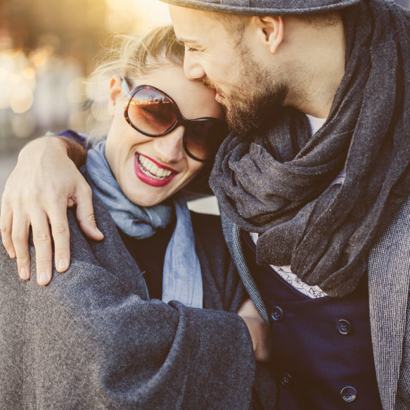 A stylish couple in fall or winter clothing smile and embrace outdoors.