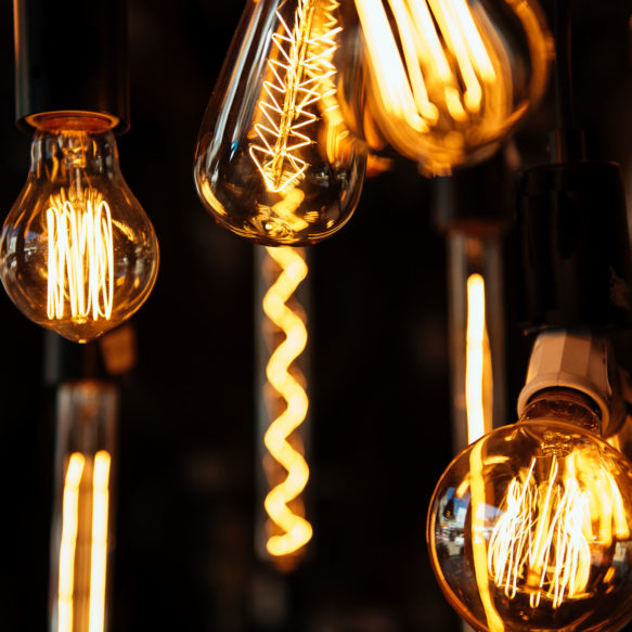 Several hanging Edison style light bulbs in varying degrees of focus hang illuminated against a dark backdrop.