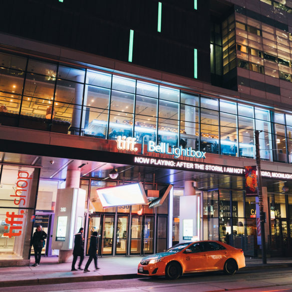 Nighttime street view of the illuminated façade of the Tiff Bell Lightbox with a taxi in front.