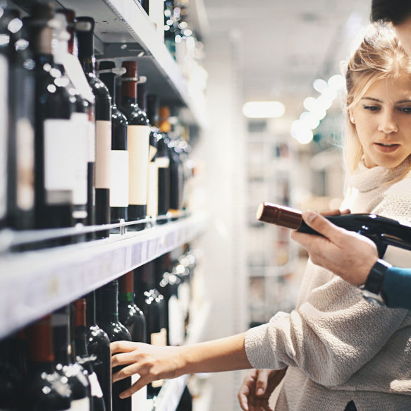 A woman standing in front of a store shelf full of red wine looks at a bottle being held by an unseen male companion.
