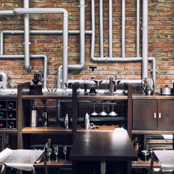 An industrial style bar featuring a worn red brick façade, excessive metal piping and dark wood wine racks.
