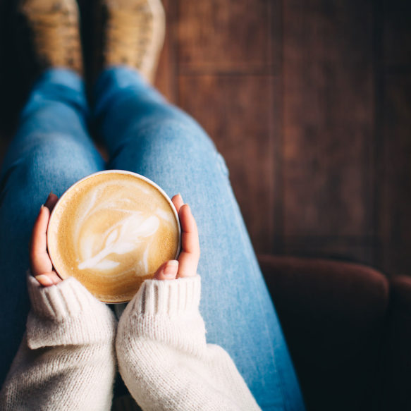 Overhead view of a woman in a cozy sweater cupping a latte in her hands.