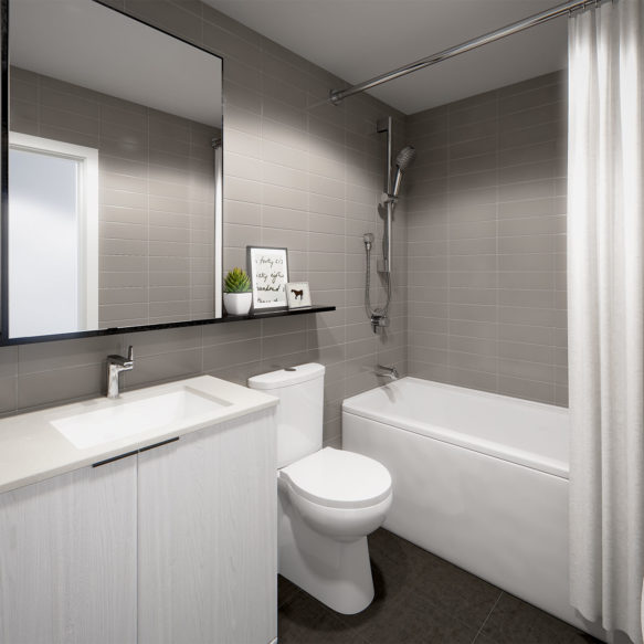 A bright contemporary bathroom featuring white fixtures and a white vanity, and grey tile walls.