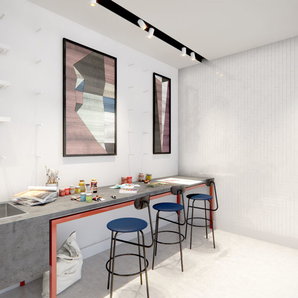A bright white artist studio featuring a grey stone counter with a large sink, bar style counter seating and art supplies.