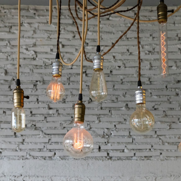 A grouping of Edison style light bulbs hang illuminated in front of a worn white brick façade.