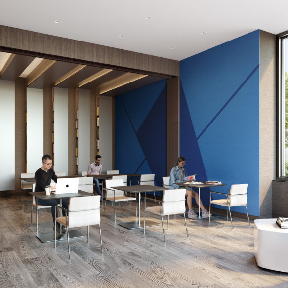 Three individuals sit at café-style tables in a bright coworking space with a blue wall and blue seating.