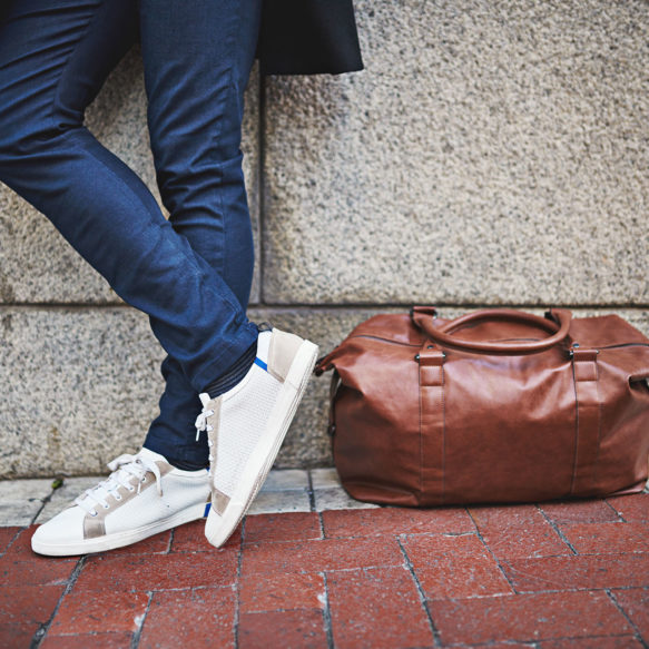 The legs of a man stand crossed in front of a grey building façade and a brown leather duffle bag sits on the ground next to his feet.