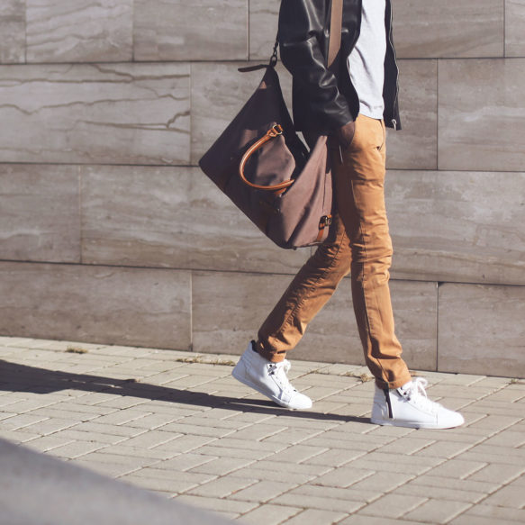 A man in beige pants and white sneakers casts a long shadow in front of marble wall as he walks with a large canvas duffle bag.