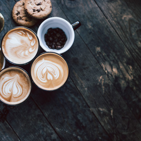 An overhead view of a collection of lattes and cookies on a worn wooden surface.