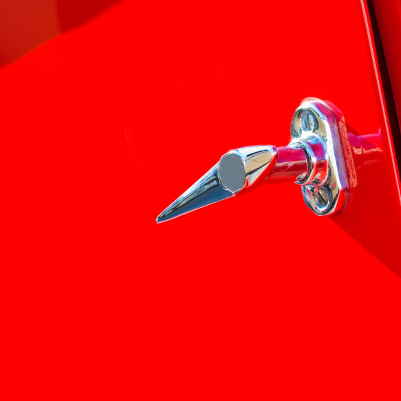 A bright red vintage car door featuring a polished chrome door handle.