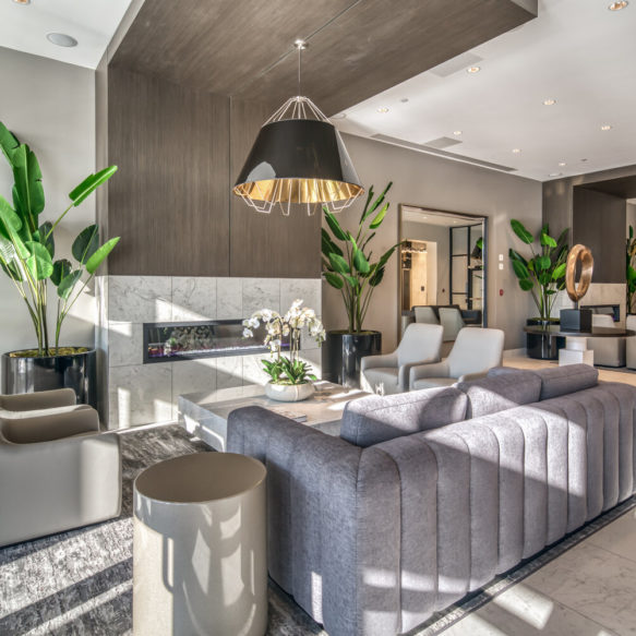 Bright interior of Brio rental residence lobby, featuring grey furniture, fireplace and plants.