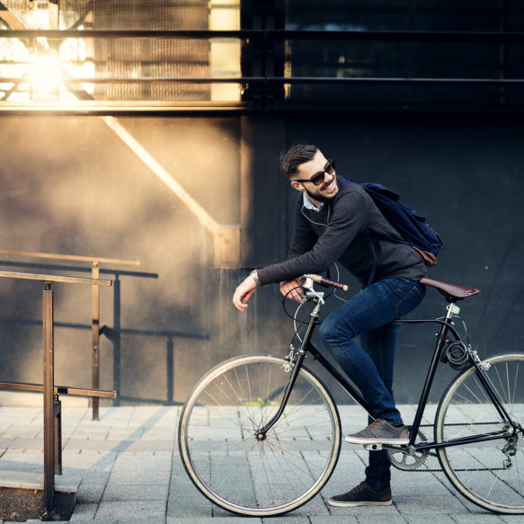 A man in jeans and a grey sweater is stopped on his bicycle, looking backwards, in front of an industrial looking wall.
