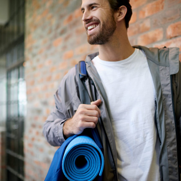 A smiling man in a grey windbreaker holds a rolled up blue yoga mat while standing in front of a red brick façade.