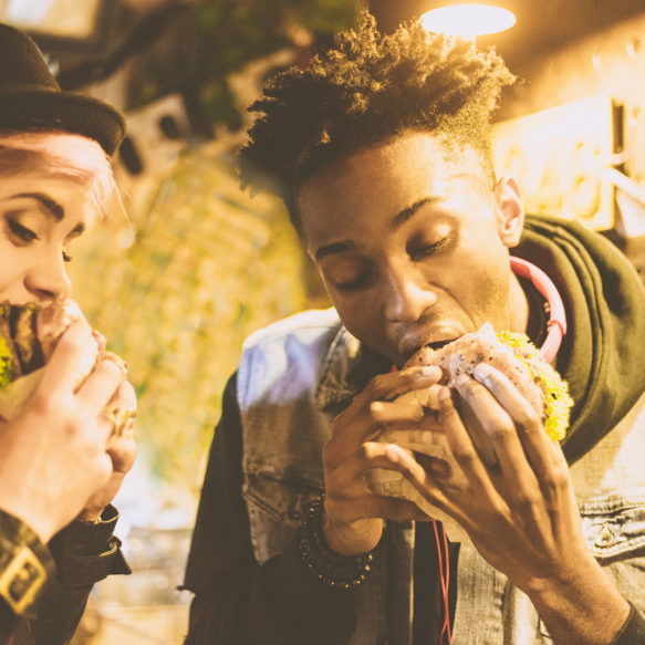 Two young people in alternative dress bite into large hamburgers.