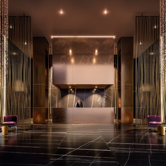 Lobby featuring gold concierge desk at the end of a long gold hallway with ornate wall and column details.