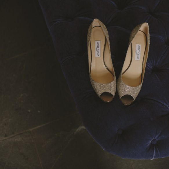 Overhead view of a pair of gold women's high heels on a navy blue tufted seat on a black slate floor.