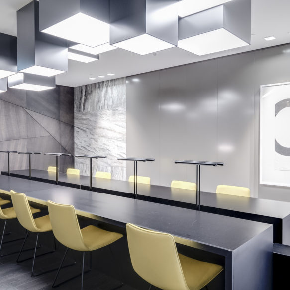A bright grey boardroom with marble walls and a large table with light yellow seating featuring angular overhead lighting.