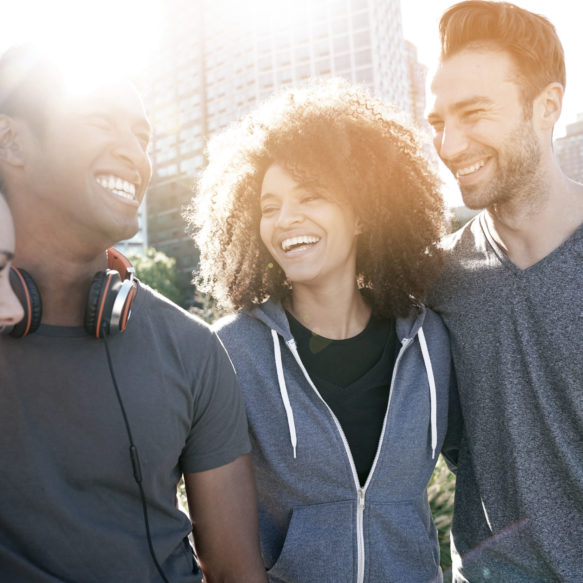 Three friends, two male and one female, laugh in an outdoor setting with the sun behind them.