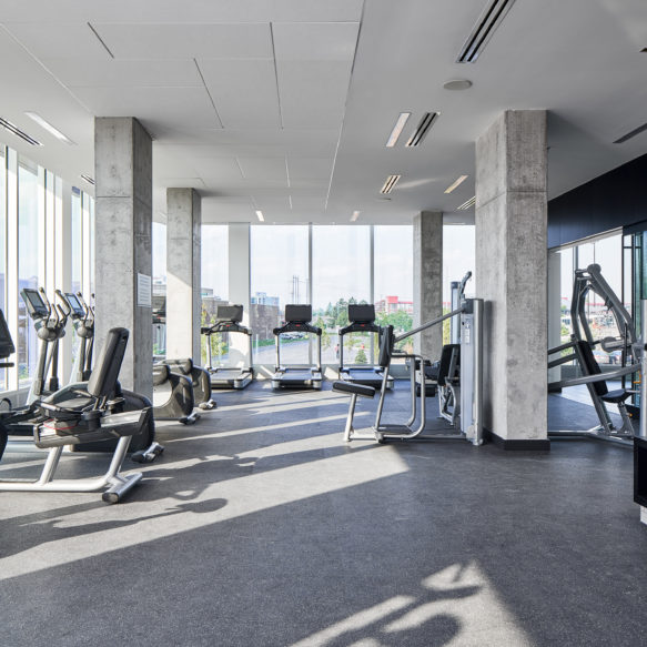 Modern fitness centre featuring stationary bikes, treadmills and floor-to-ceiling windows with street views.