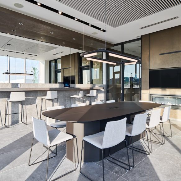 Bright shared workspace featuring large central table, white chairs, bar seating and fireplace.