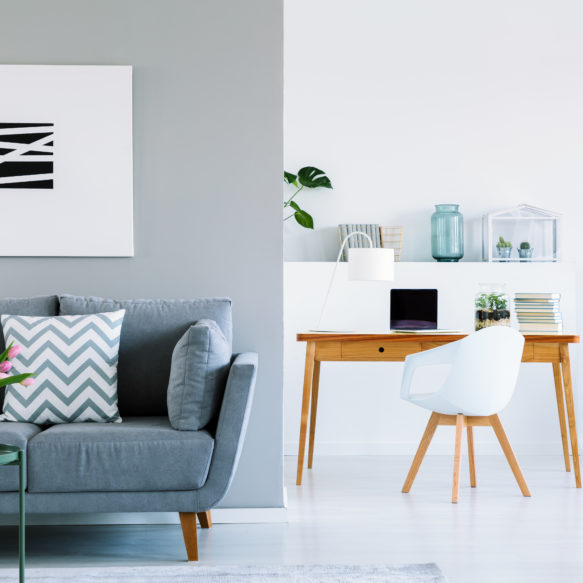 Suite featuring blue couch with patterned pillows, grey walls, abstract painting and home office.