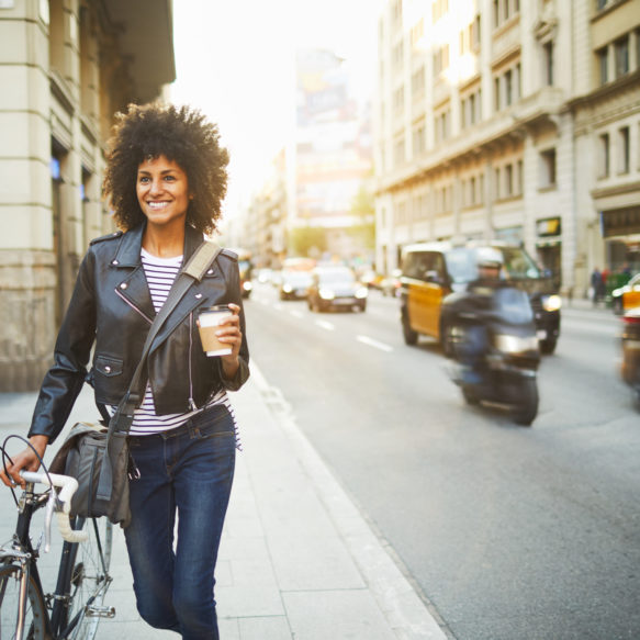 Woman in leather jacket holding coffee walks bicycle down a busy sidewalk at sunset.
