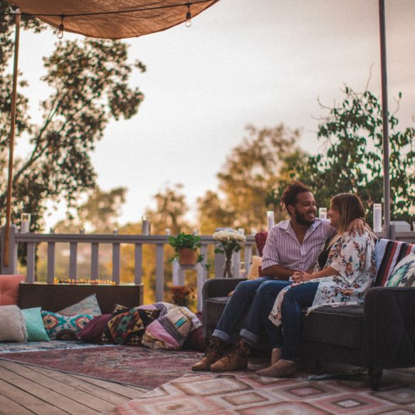 Couple sitting on couch on elevated deck decorated with lots of eclectic rugs and pillows.