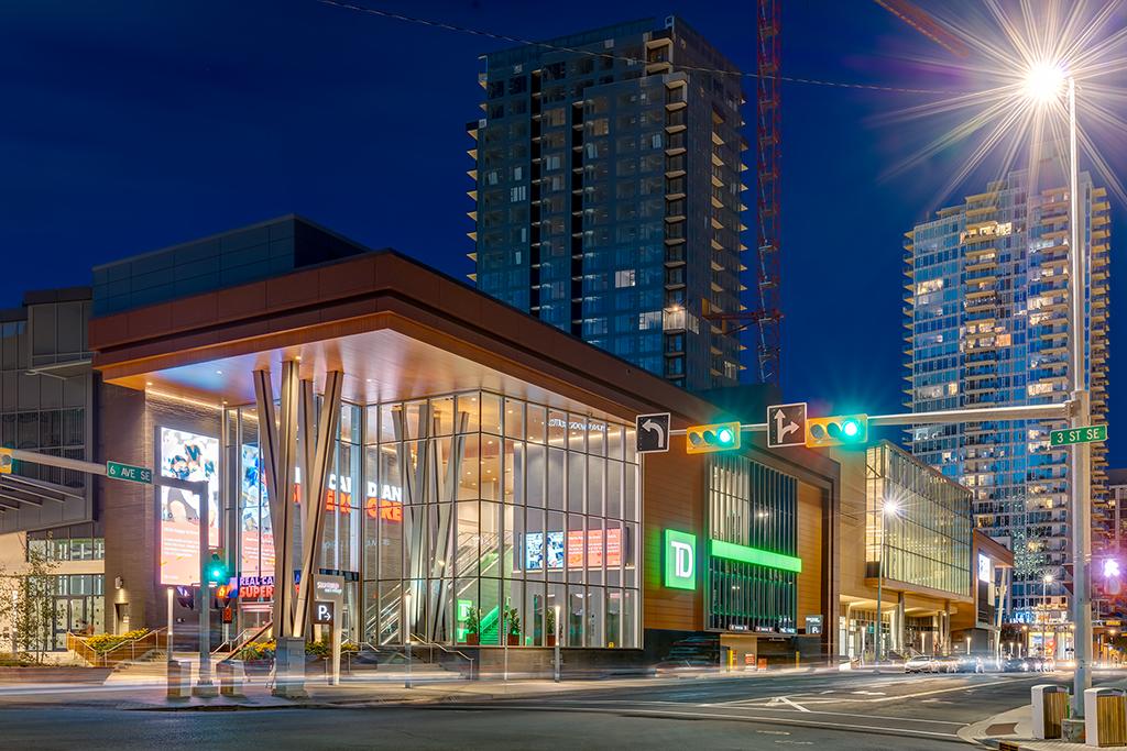 Evening street view of brightly lit retail podium.